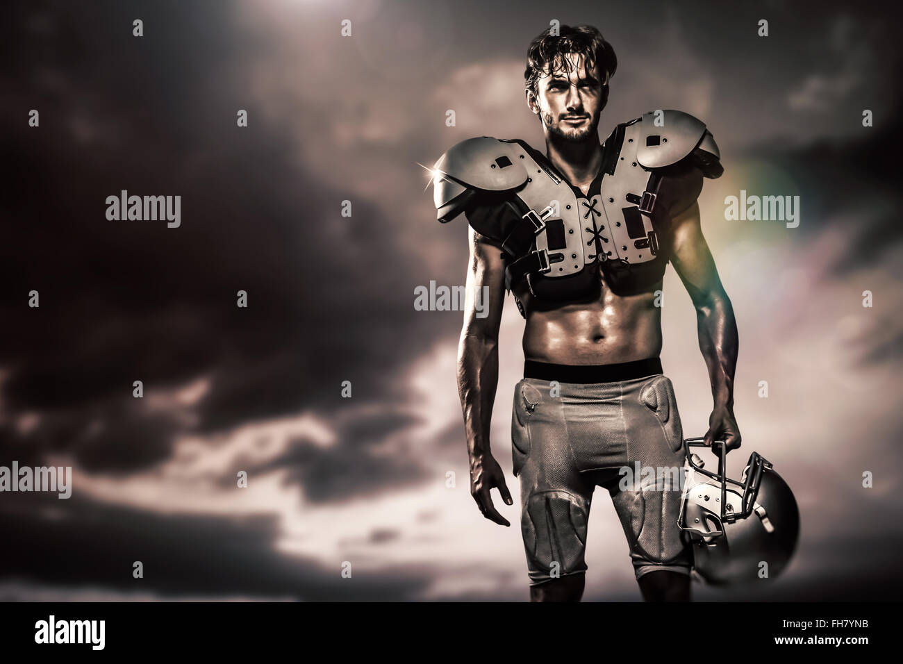 Composite image of shirtless american football player with padding holding helmet - Stock Image