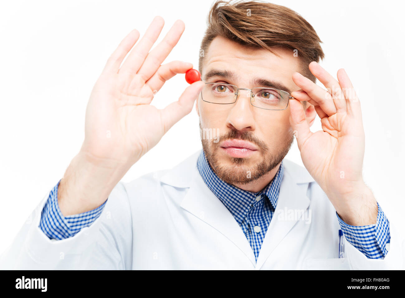 Young male doctor in glasses looking on pill isolated on a white background - Stock Image