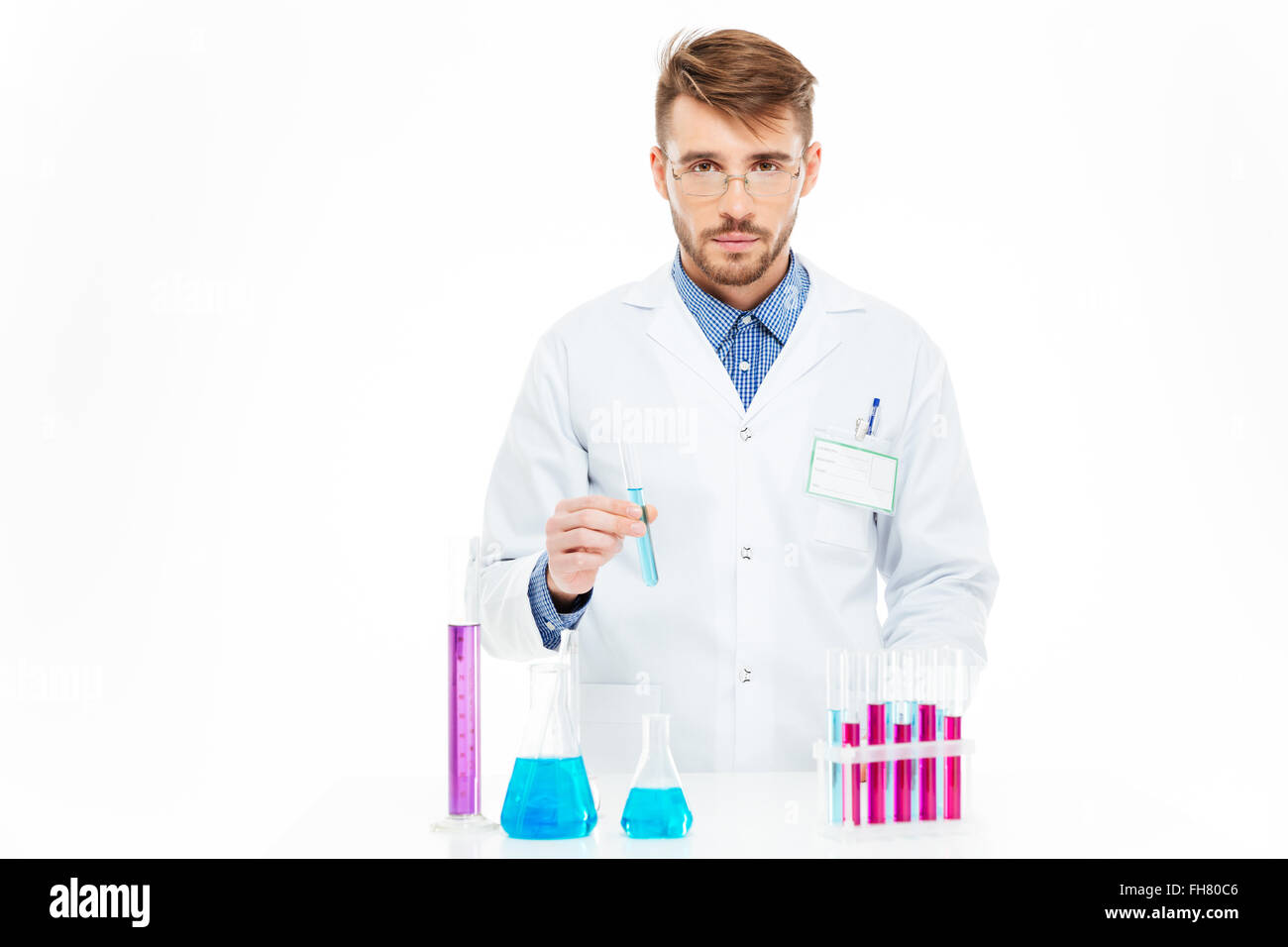 Scientist pouring chemicals in a laboratory - Stock Image