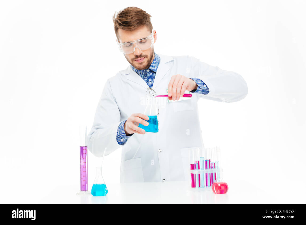 Man pouring chemicals isolated on a white background - Stock Image