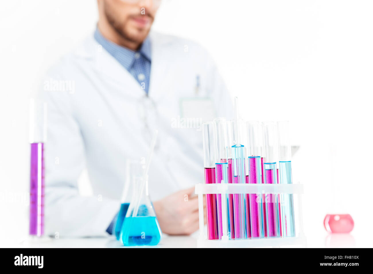 Cropped image of a scientist pouring chemicals in a laboratory - Stock Image