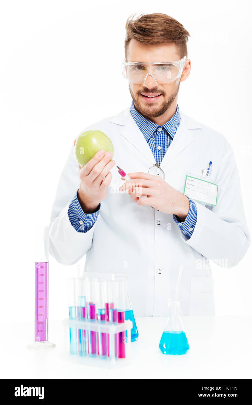 Male chemist doing injection of GMOs into apple isolated on a white background - Stock Image