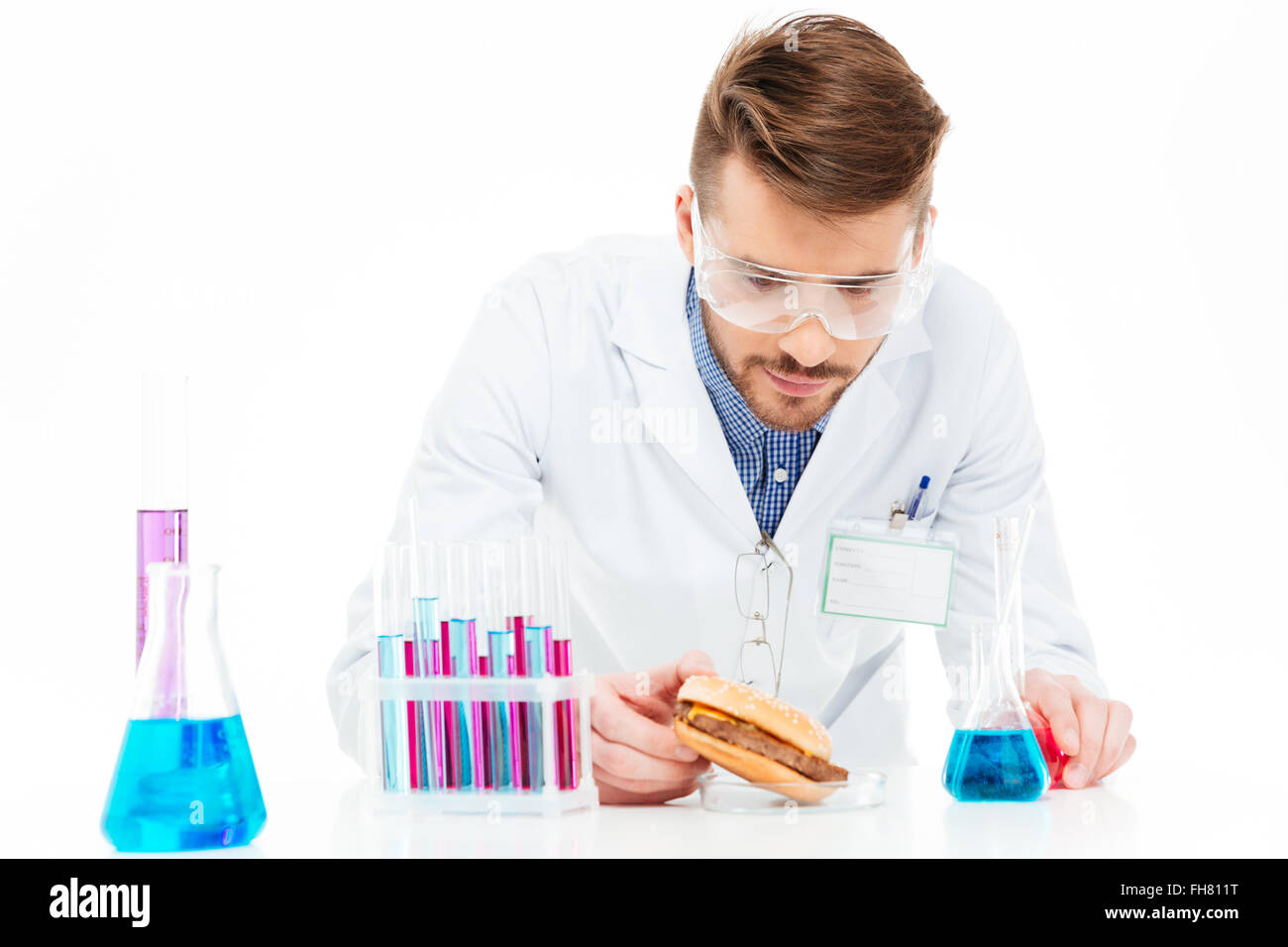 Male chemist making GMOs food isolated on a white background - Stock Image