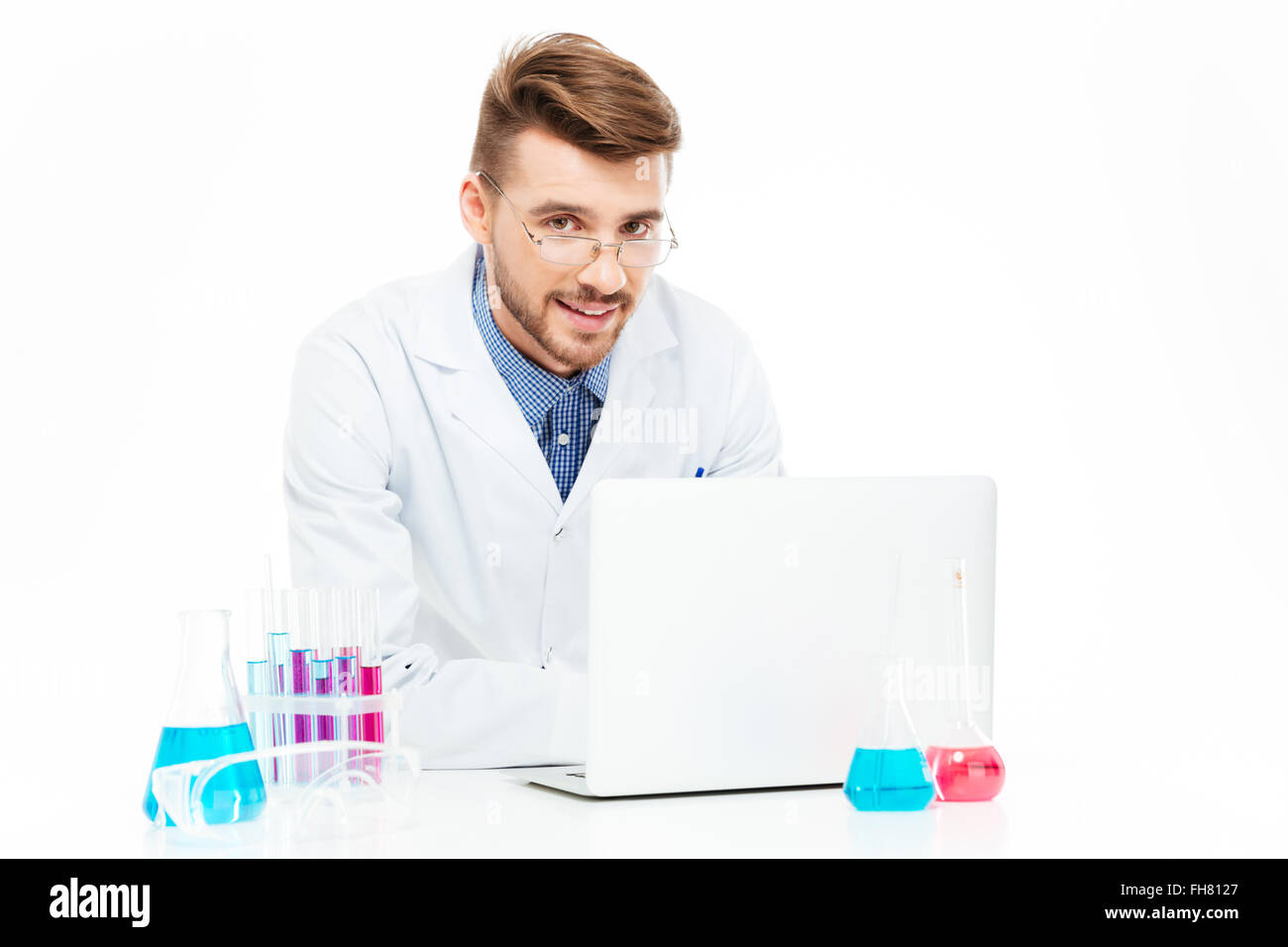 Happy chemist using laptop computer in laboratory - Stock Image