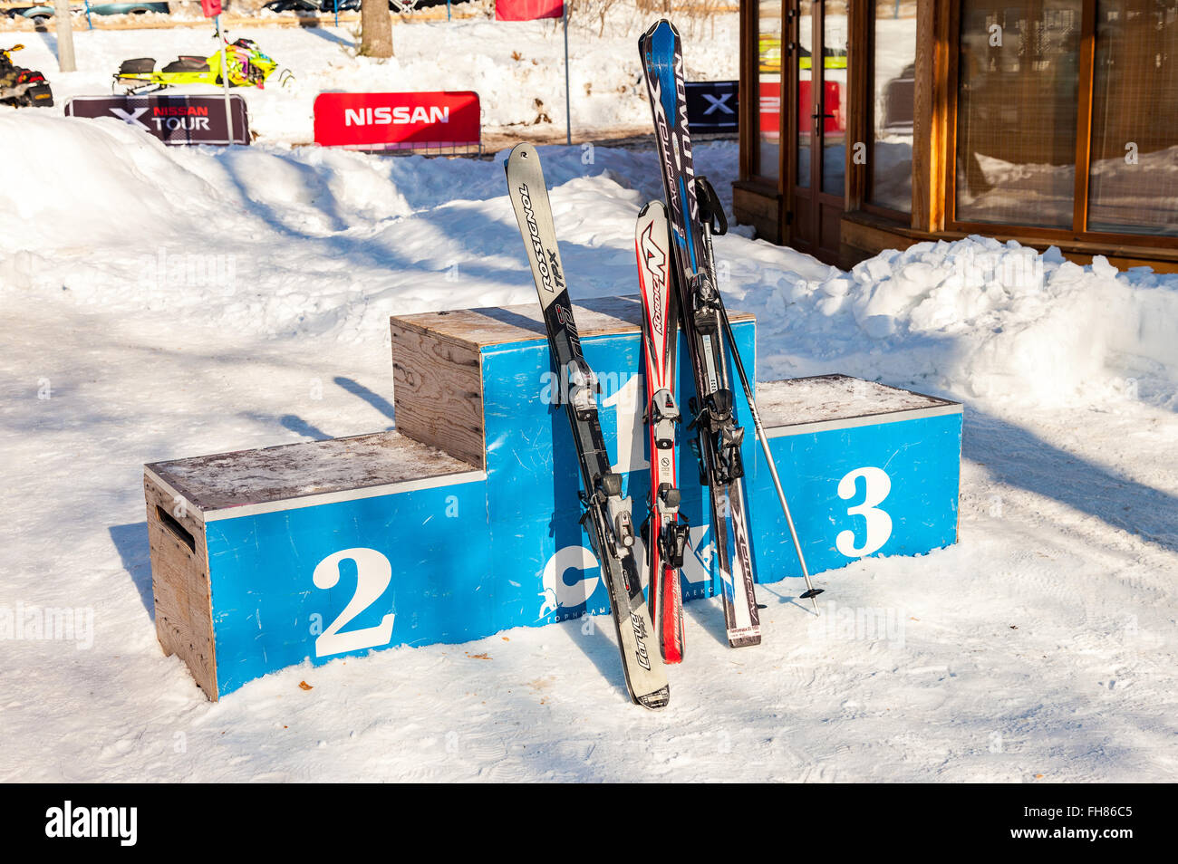 Wooden pedestal with skis at the  'Krasnaya Glinka' mountain ski resort in winter sunny day - Stock Image