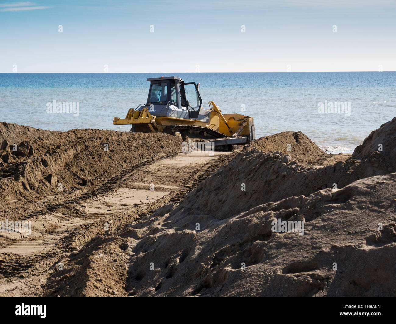 Bulldozer, Beach sand regeneration eroded by waves, Mijas Malaga province Costa del Sol. Andalusia southern Spain - Stock Image