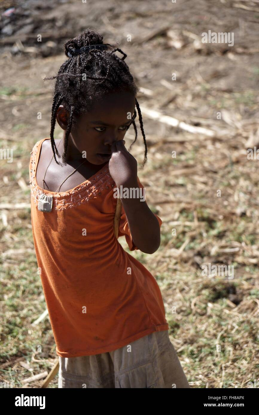 An Ethiopian girl holds a stick across her back - Stock Image