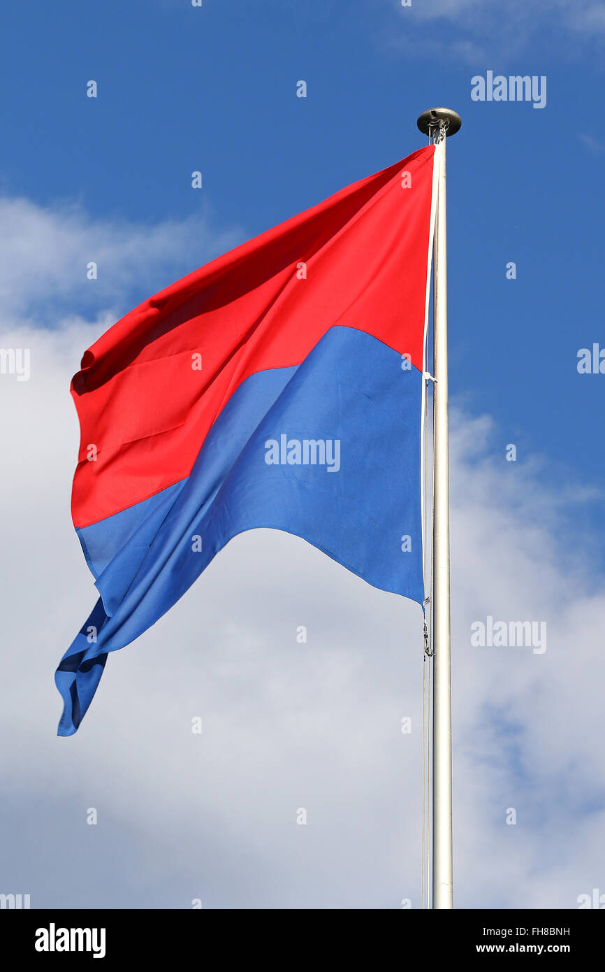 Flag of the State and Republic of Canton Ticino, Switzerland, flapping in the wind against blue skies and white Stock Photo
