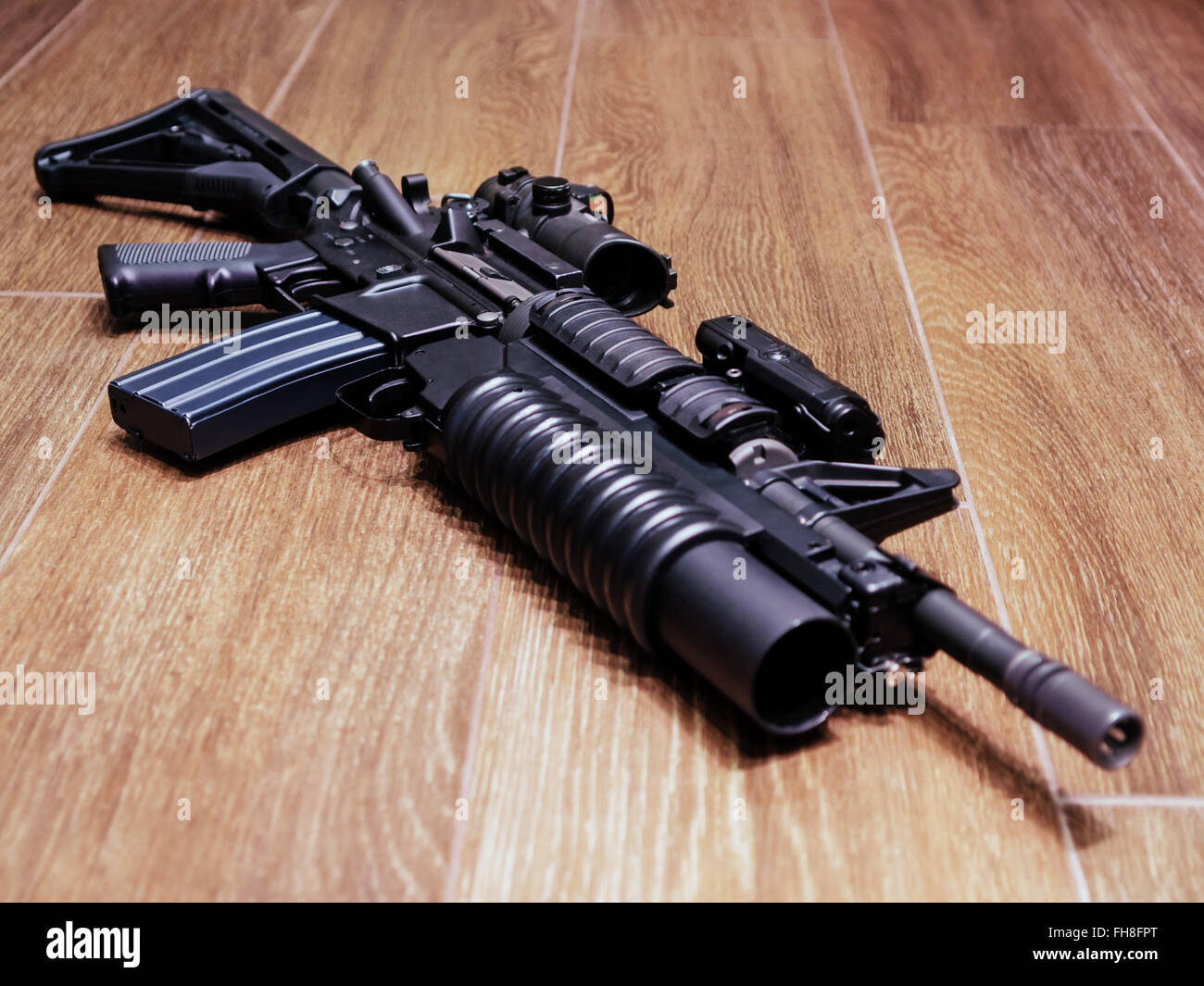 AR15 rifle with grenade launcher on the wooden floor, selective focus - Stock Image
