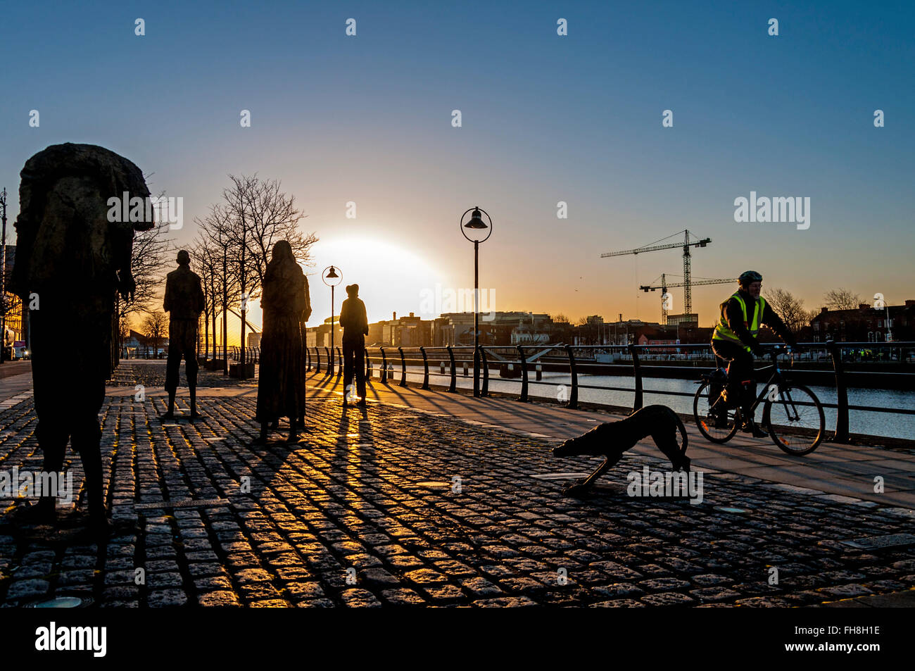 the famine memorial dublin ireland a man cycles past at sunrise