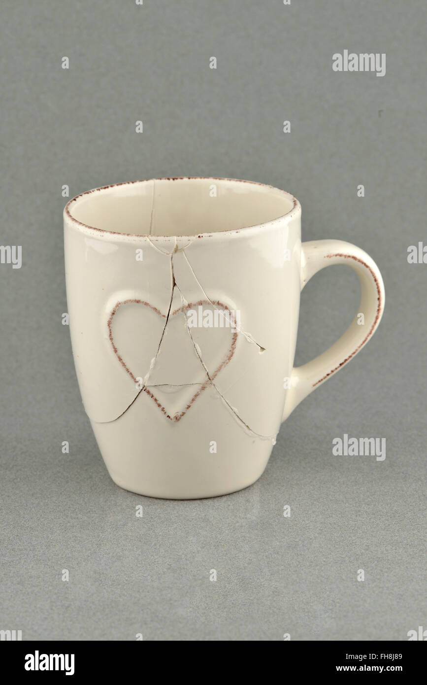 Broken and repaired coffee cup - Stock Image