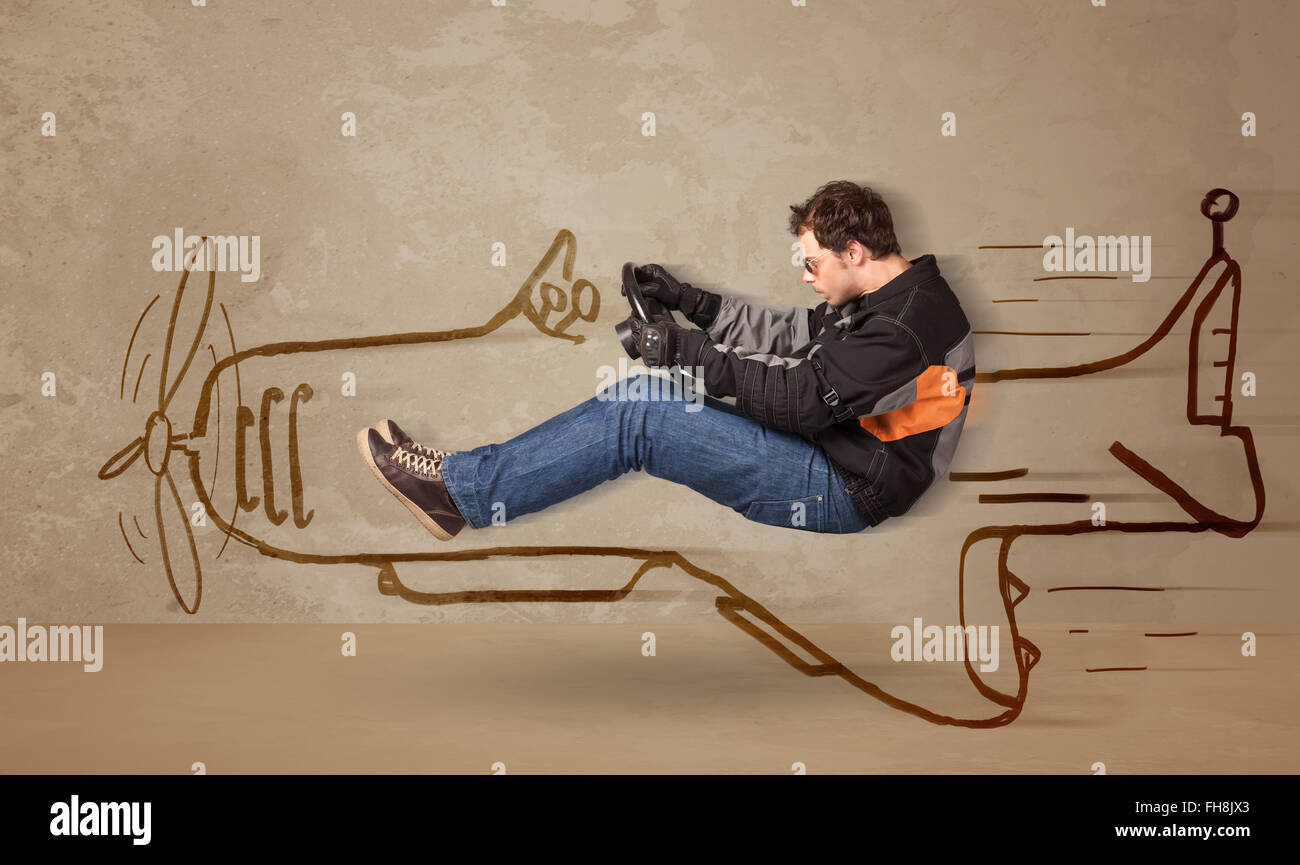 Funny pilot driving a hand drawn airplane on the wall - Stock Image