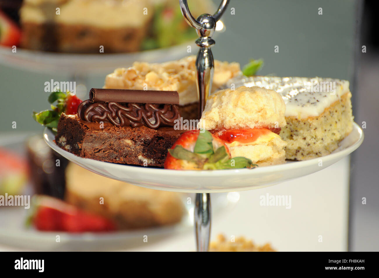 Fancy cakes on a cake stand at a buffet. Selective focus with good separation of depth. - Stock Image