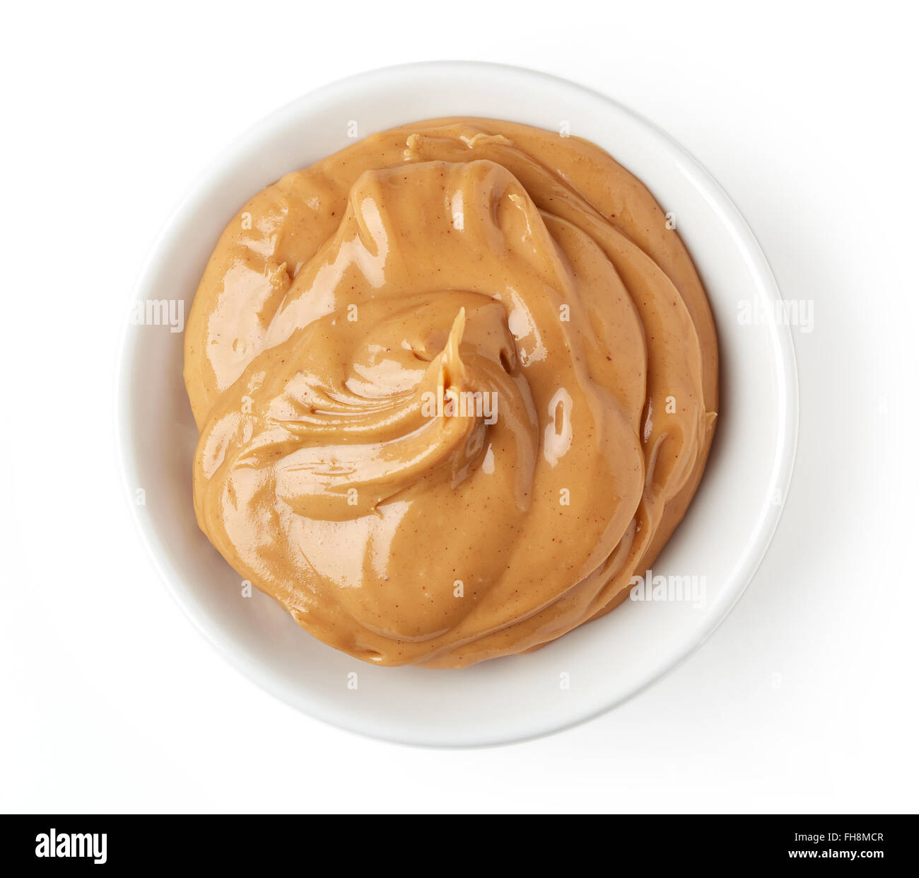 Creamy peanut butter in round dish isolated on white background, top view - Stock Image