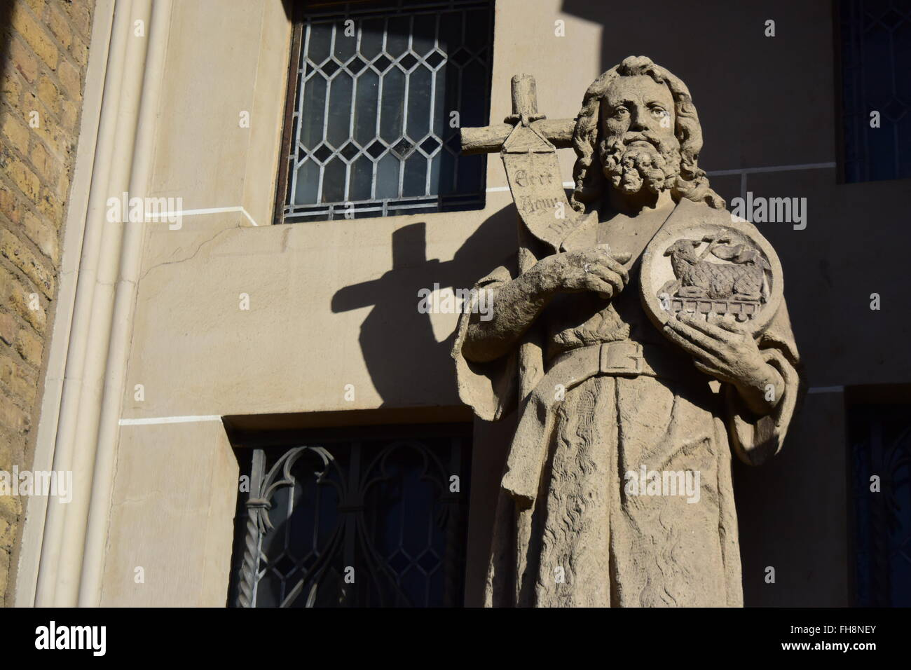 sculpture of a holy man with cross and paschal lamb - Stock Image