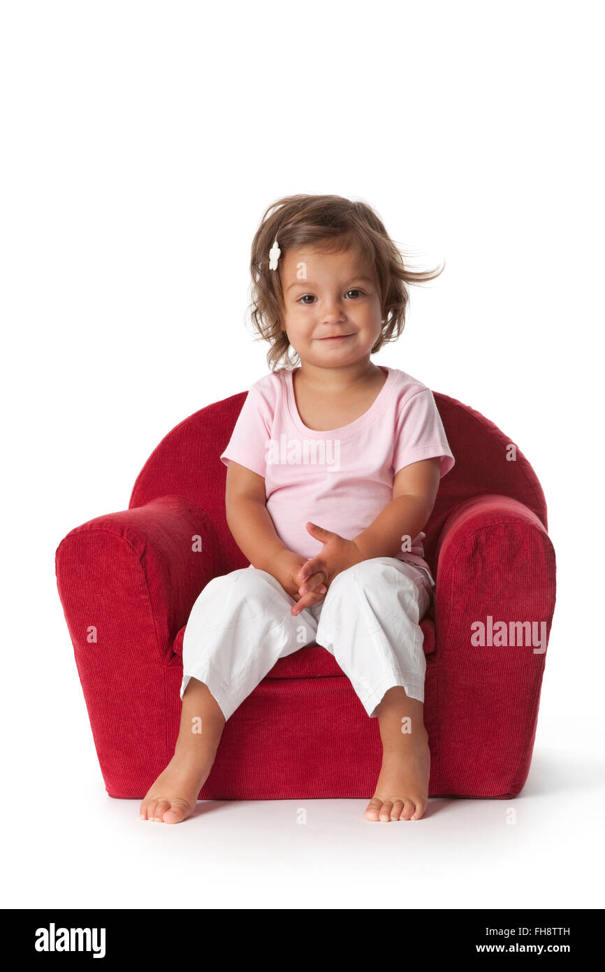 Toddler girl sitting in an armchair on white background - Stock Image