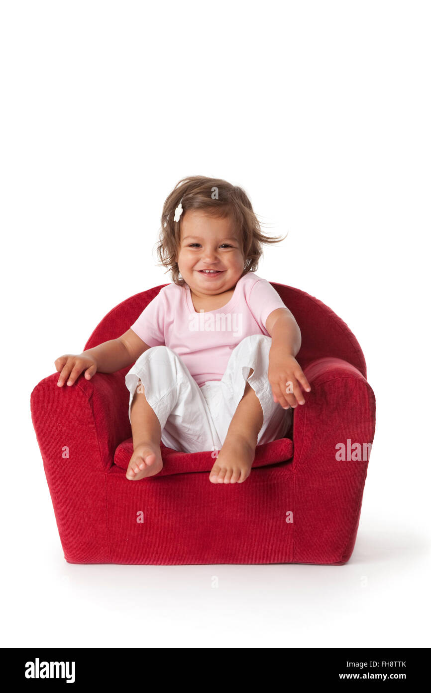 Toddler girl making fun in an armchair on white background - Stock Image