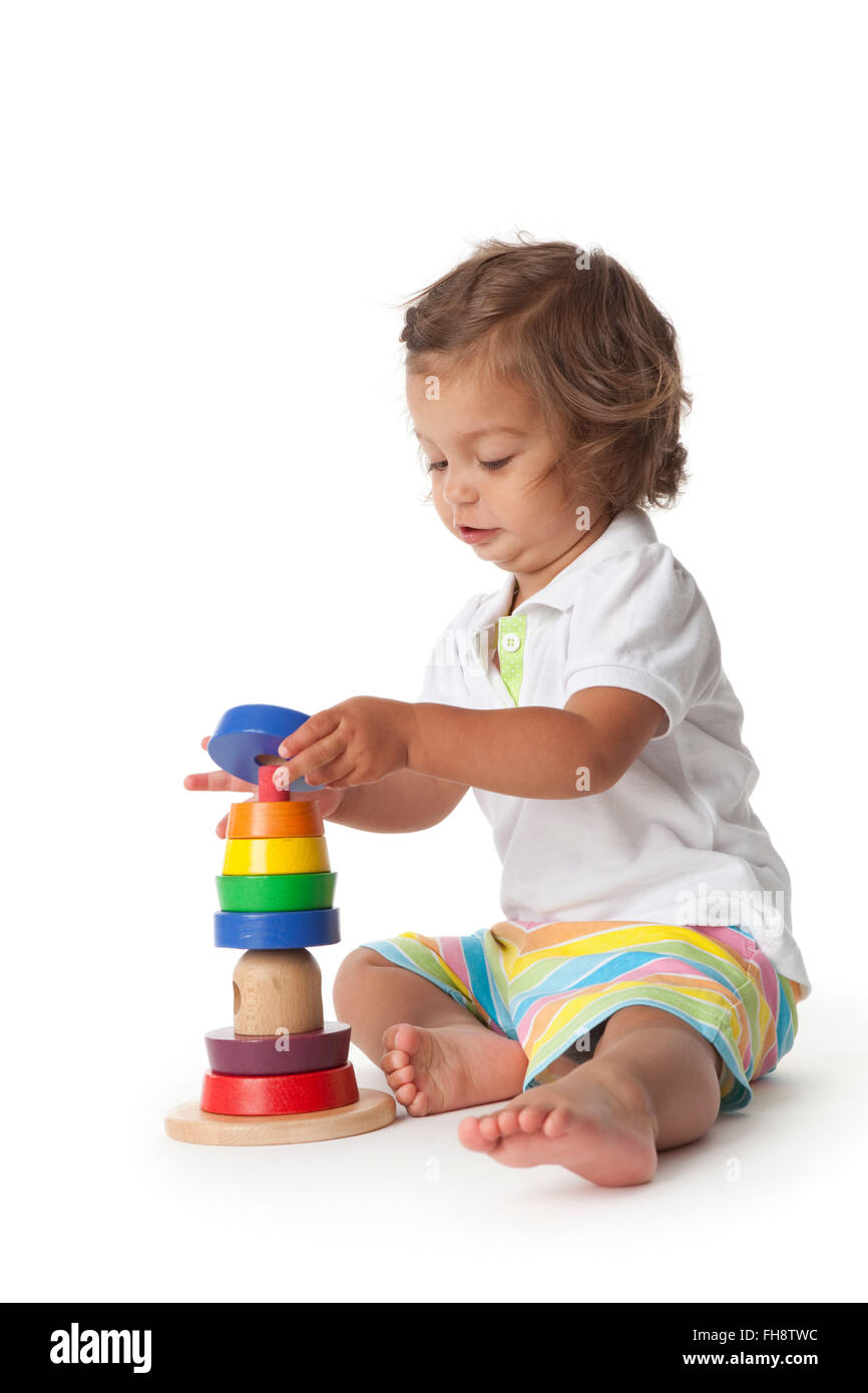 Toddler girl playing with colored bricks on white background - Stock Image