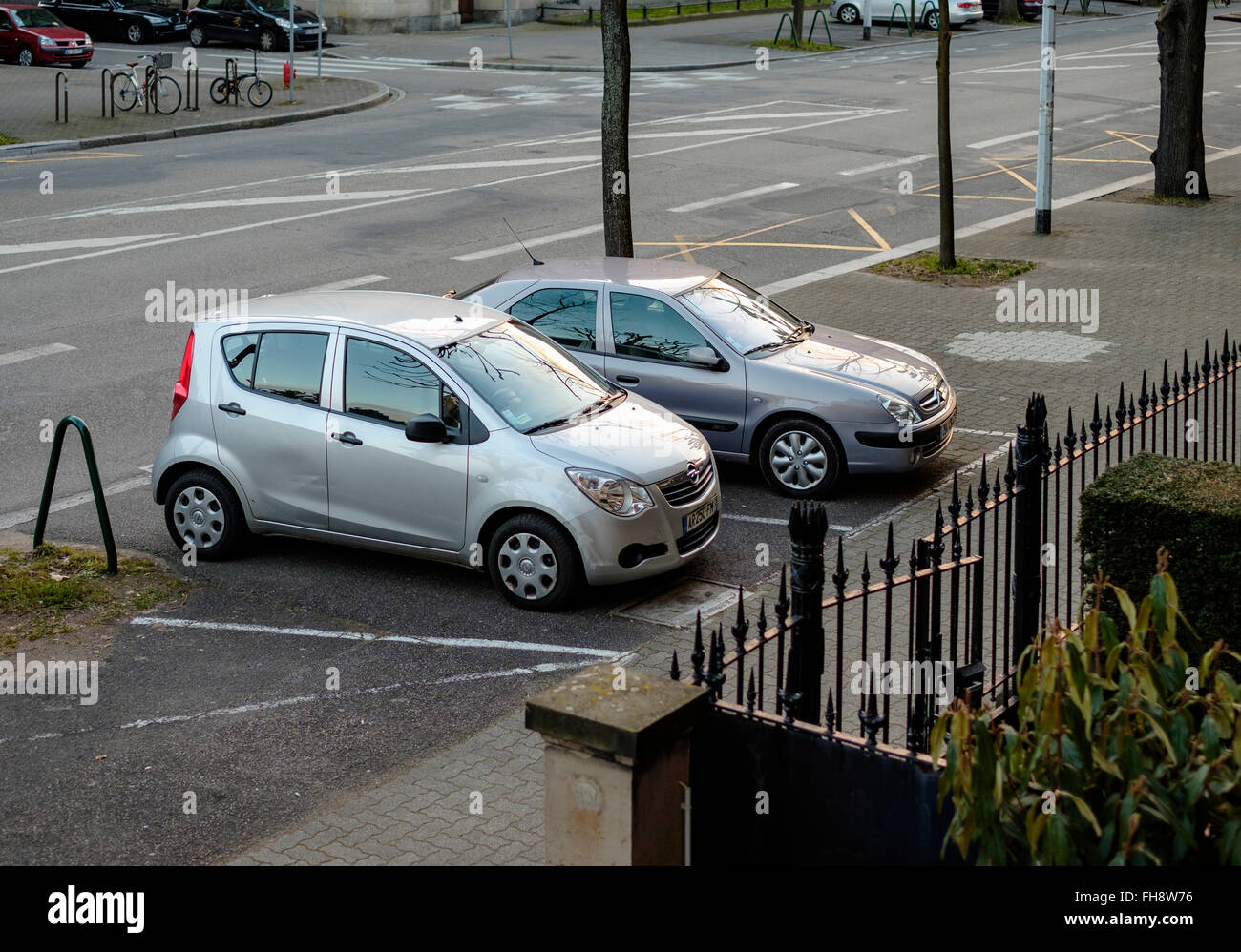 Two cars parked on pavement, Strasbourg, Alsace, France - Stock Image