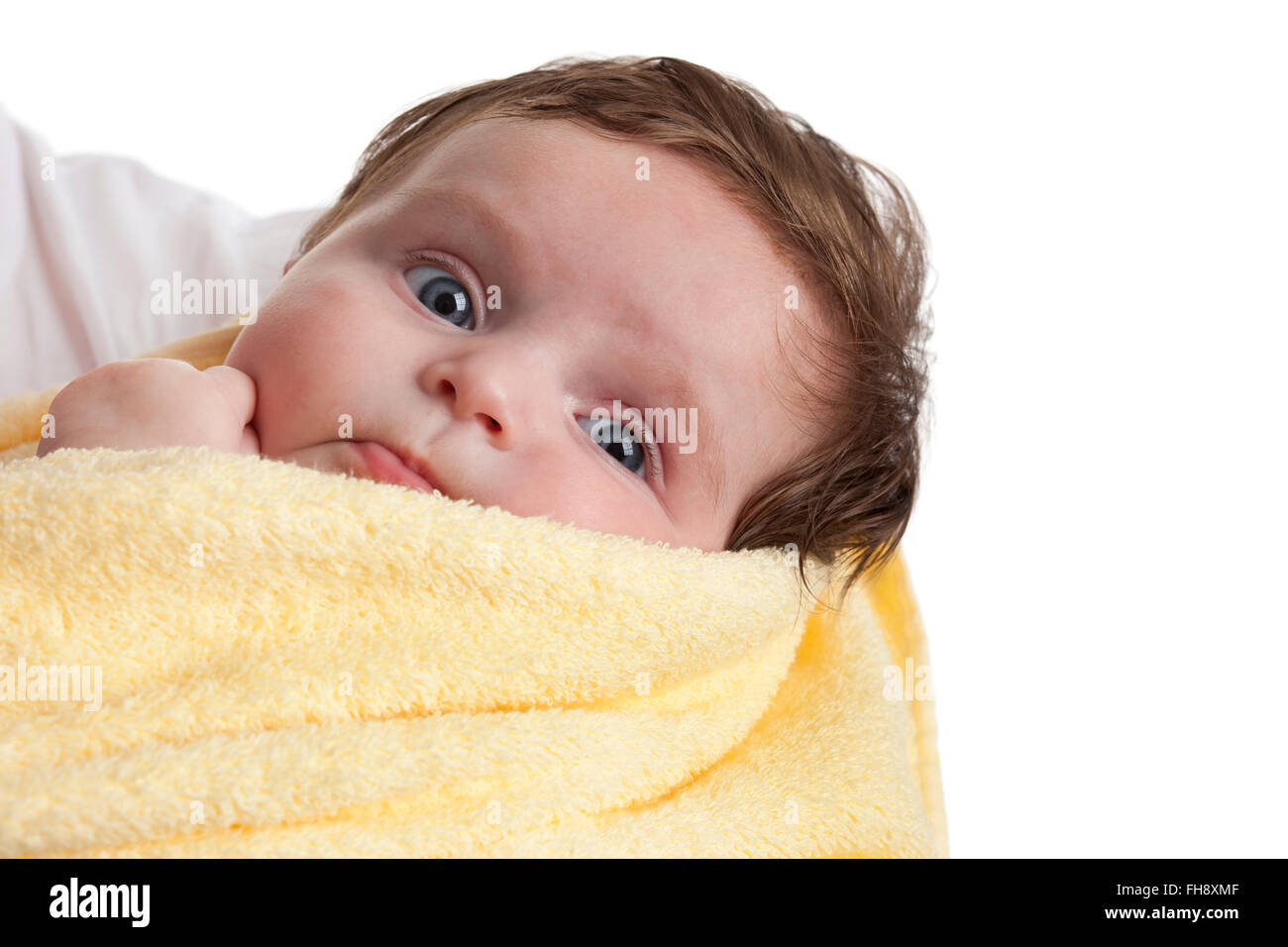 Cute little baby girl wrapped in a yellow towel on white background - Stock Image