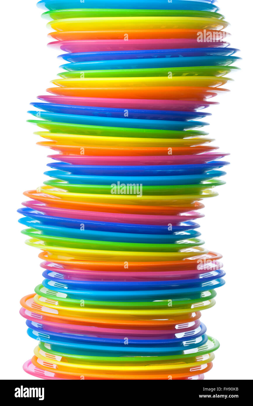 Rainbow colored plastic plates on white background - Stock Image