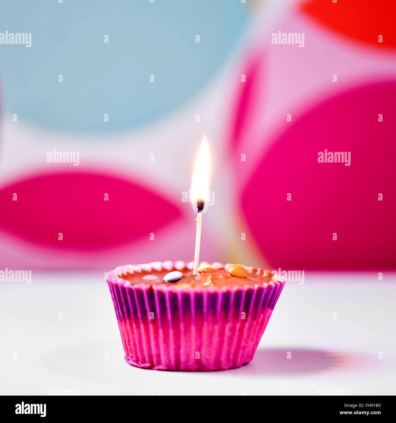 a chocolate cupcake topped with a lighted match on a white surface against a colorful geometric-patterned background - Stock Image