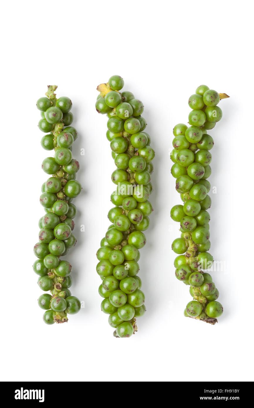 Strings of fresh unripe green pepper on white background - Stock Image