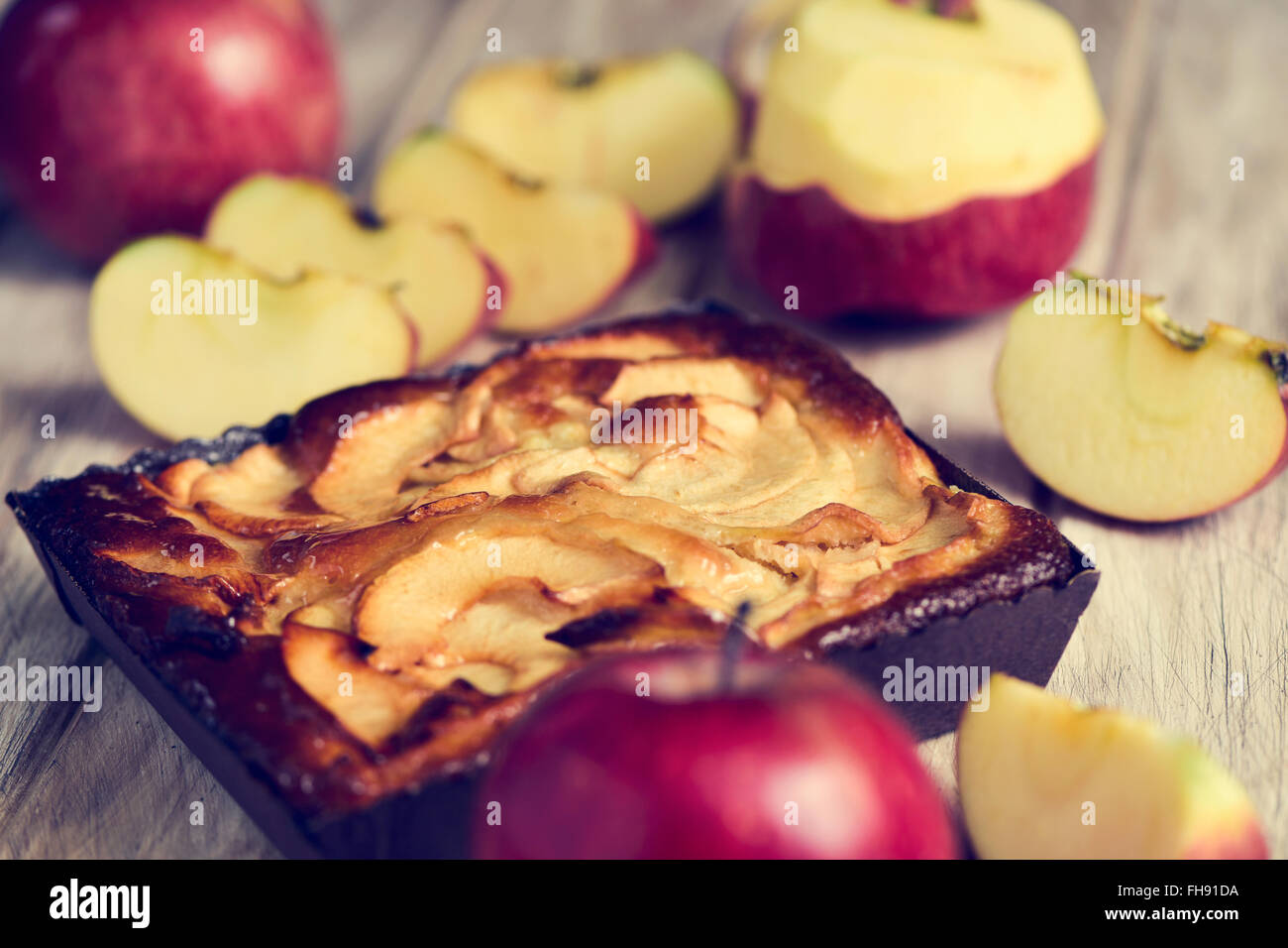 closeup of an apple cake and some red apples on a rustic wooden table - Stock Image