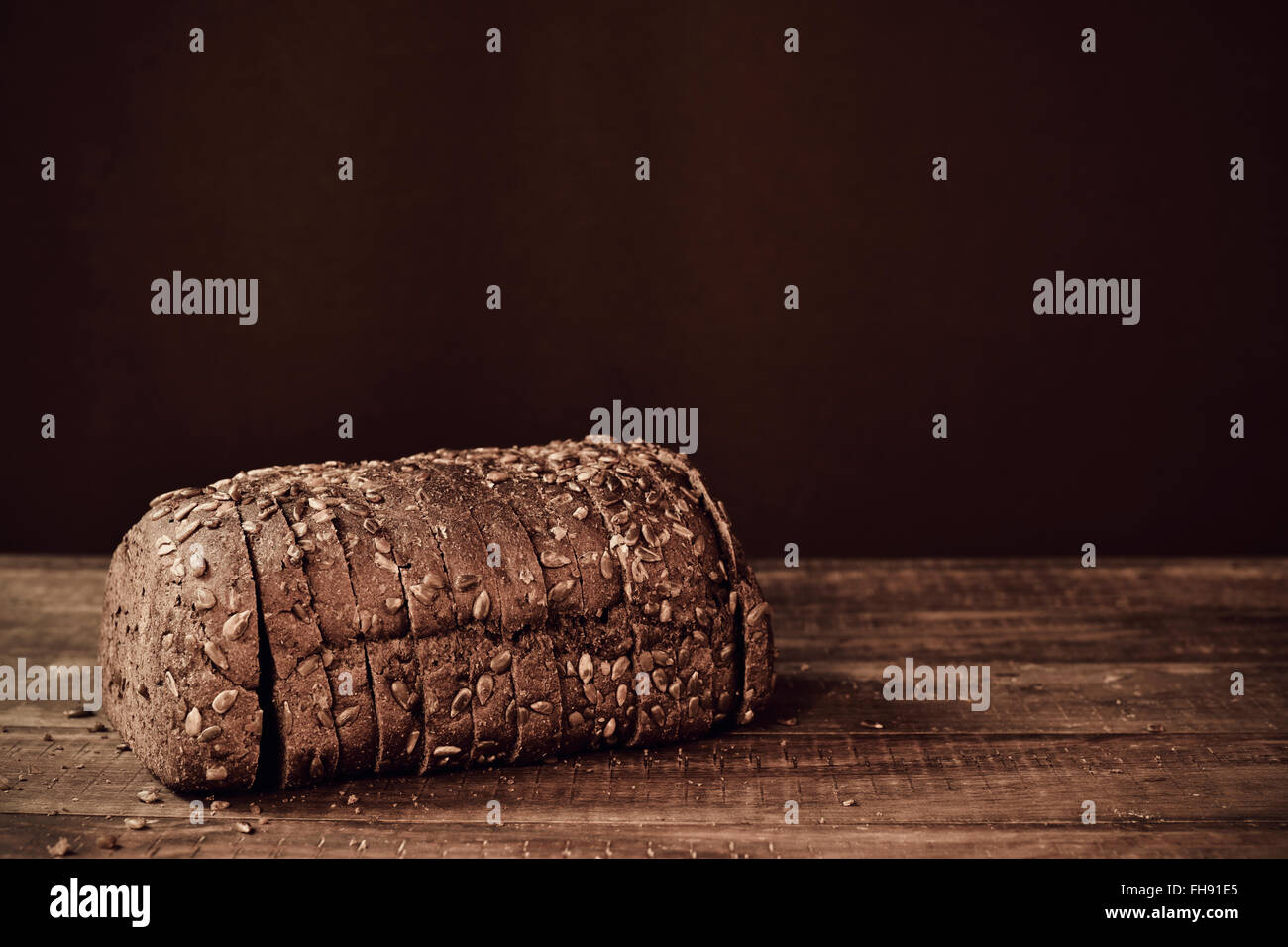 a sliced loaf of rye bread topped with sunflower seeds on a rustic wooden surface, in sepia toning - Stock Image