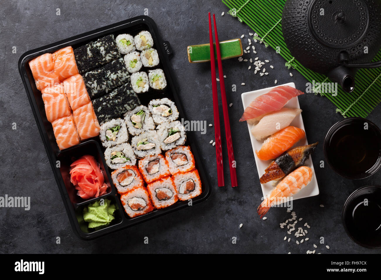Set of sushi and maki roll and green tea on stone table. Top view - Stock Image