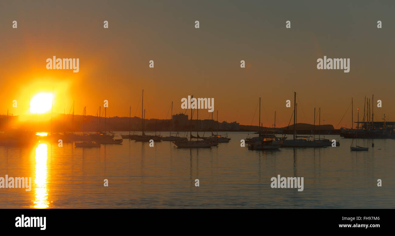 Magnificent sunset color in marina harbor.  End of a warm sunny day in Ibiza, St Antoni de Portmany Balearic Islands, - Stock Image