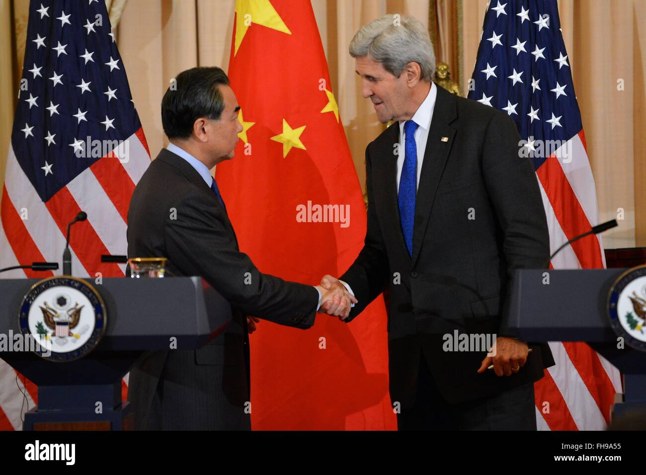 U.S. Secretary of State John Kerry shakes hands with Chinese Foreign Minister Wang Yi after a joint news conference - Stock Image