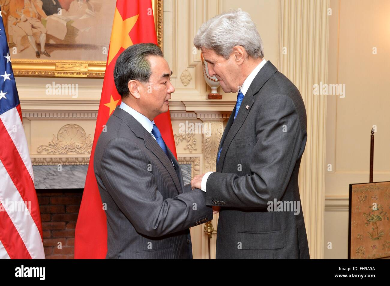U.S. Secretary of State John Kerry greets Chinese Foreign Minister Wang Yi before their bilateral meeting at the - Stock Image
