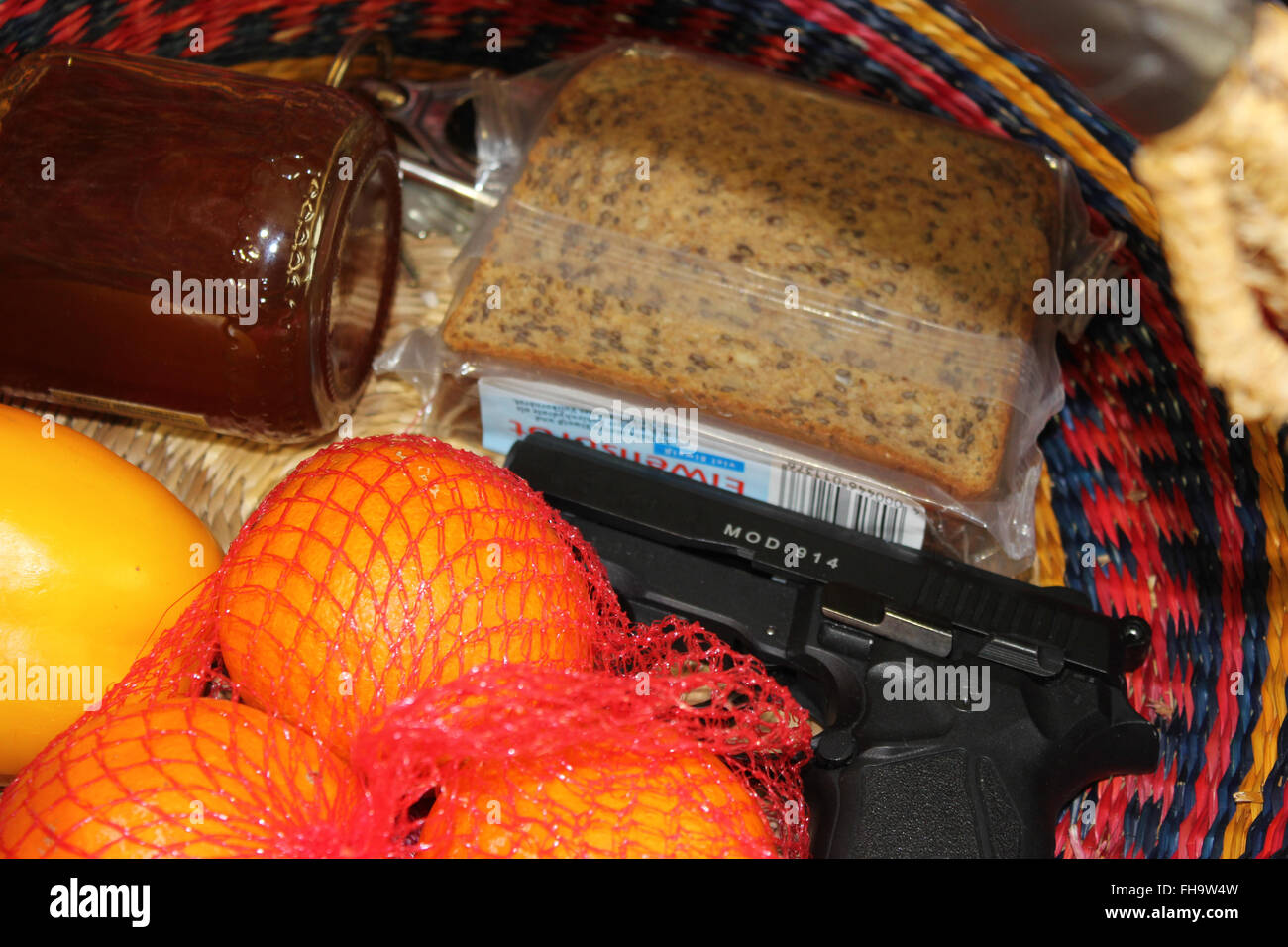 Carried concealed. Handgun and accessories in a shopping basket. - Stock Image
