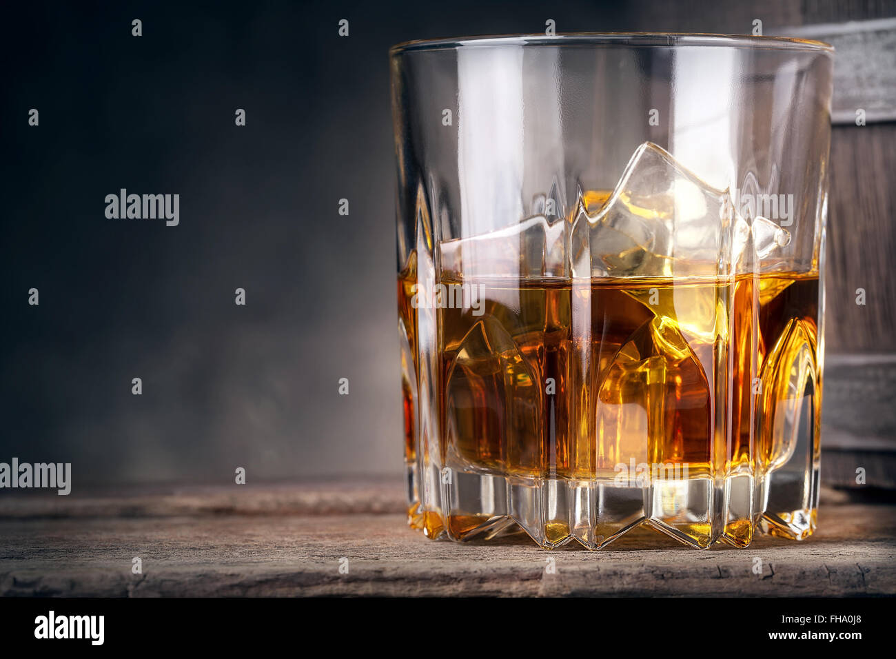 Glare glass of whiskey with ice and barrel in the background - Stock Image