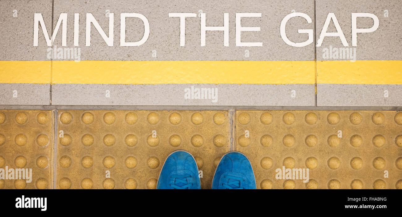 The sign ' Mind the gap ' painted on train station's platform edge - Stock Image