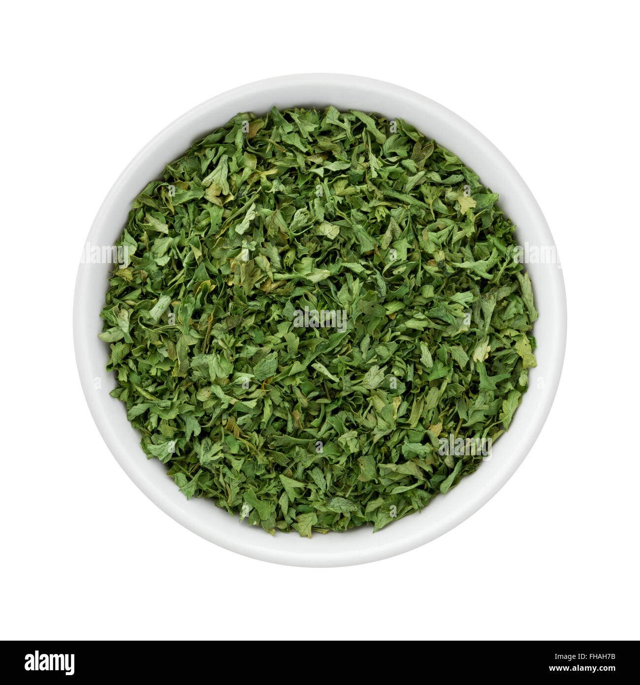 Dried Parsley Flakes in a Ceramic Bowl. The image is a cut out, isolated on a white background. - Stock Image