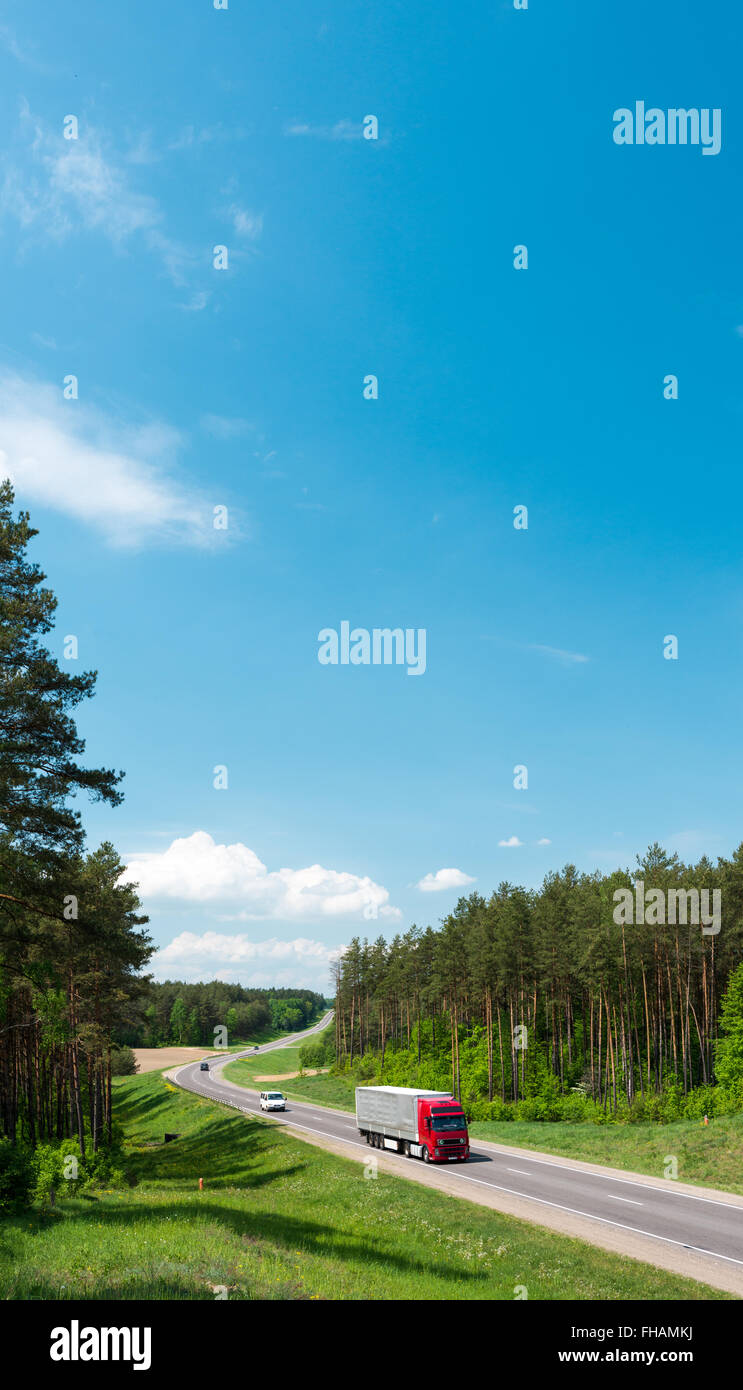 Truck and cars on country road in forest in Belarus. Blue sky with clouds in background. Beautiful and sunny summer - Stock Image