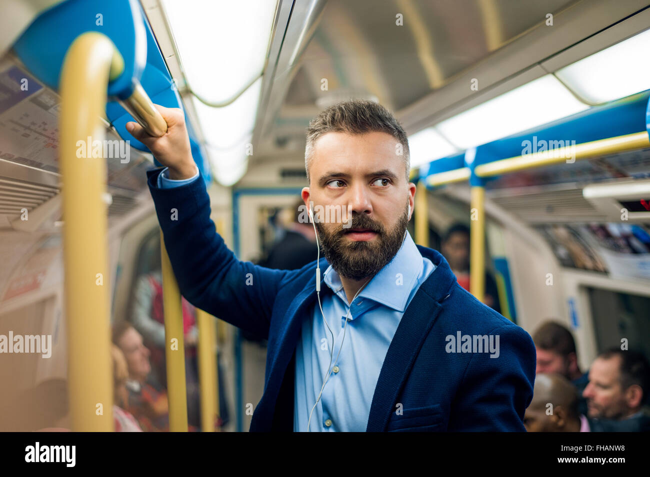 Serious businessman travelling to work. Standing inside undergro - Stock Image