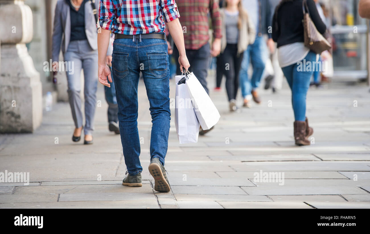 Unrecognizable man with shopping bags in the street, back view - Stock Image