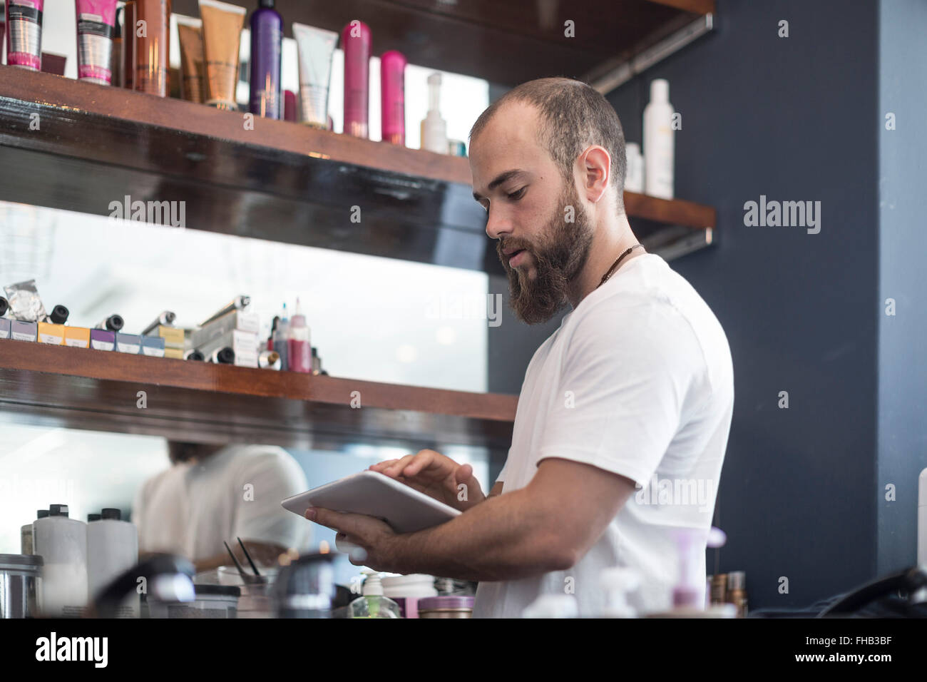 Barber doing shop inventory with digital tablet - Stock Image