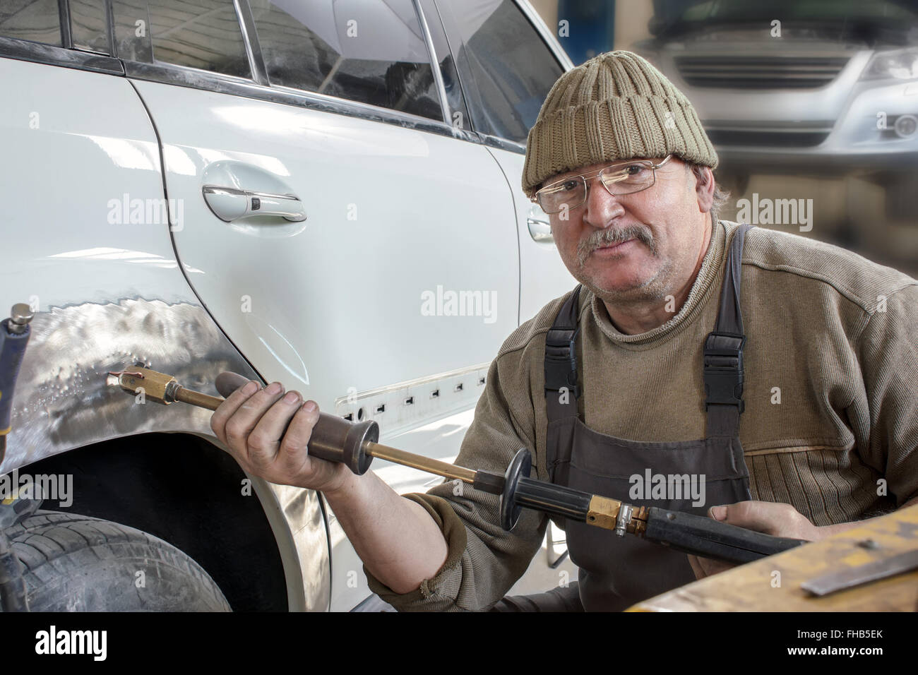 Portrait of a happy middle-aged worker in his workshop. Stock Photo