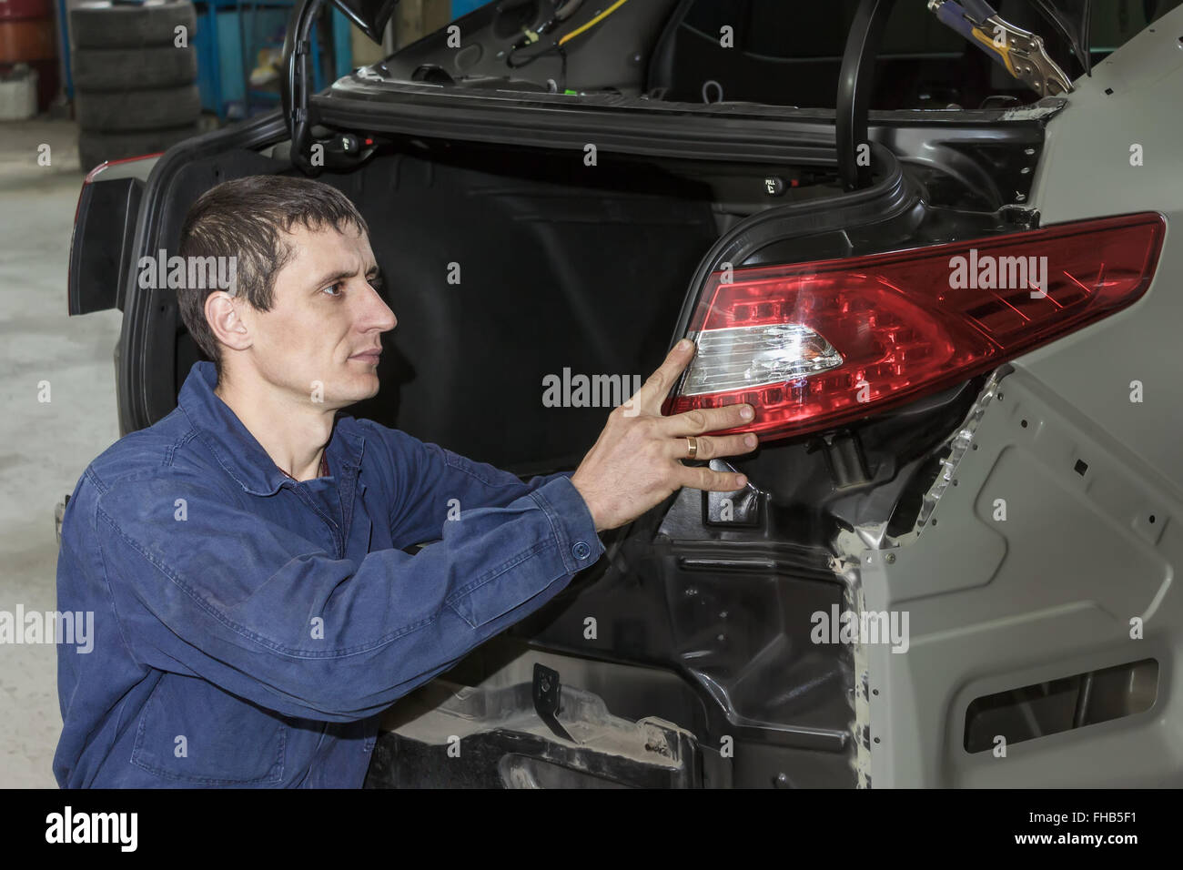 Young mechanic installs tail light on the vehicle. Stock Photo
