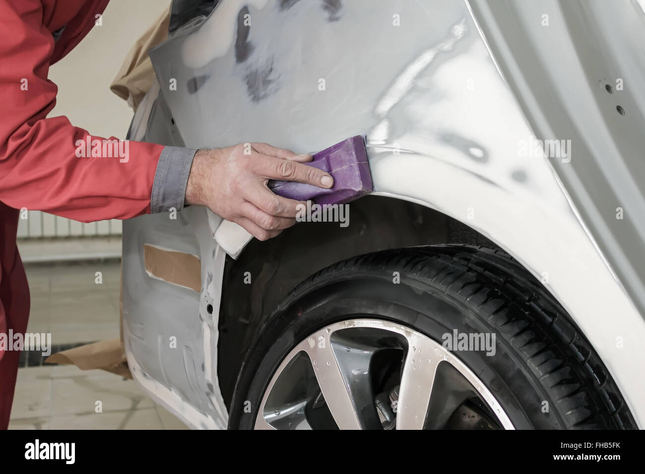 Car painter prepares the rear wing of the car for painting. - Stock Image