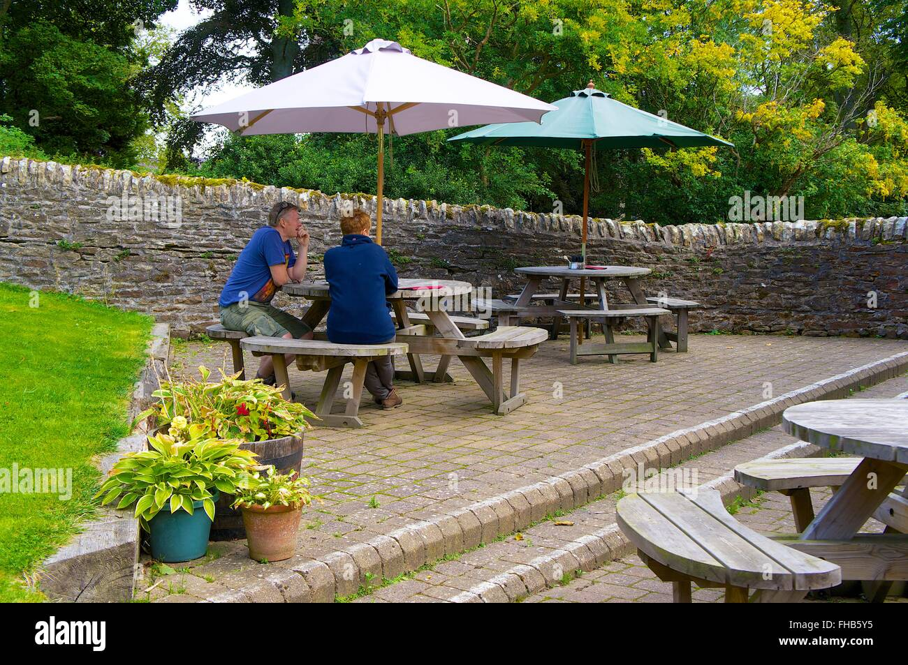 Northumberland Middle Aged Couple Sitting At Picnic Table Under - Picnic table parasol