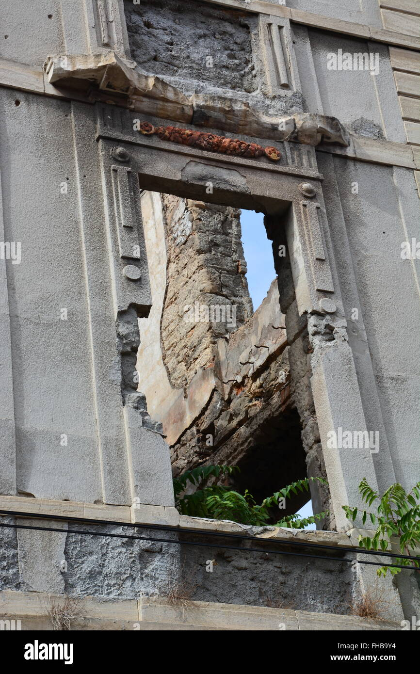 The vacant window of a building destroyed during the Bosnian War in Mostar. - Stock Image
