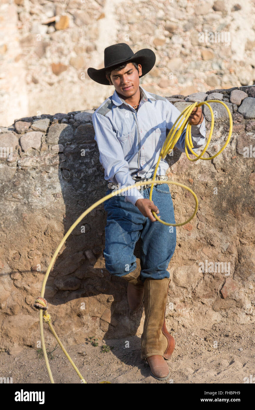 A Mexican charro or cowboy poses in cowboy hat and lasso