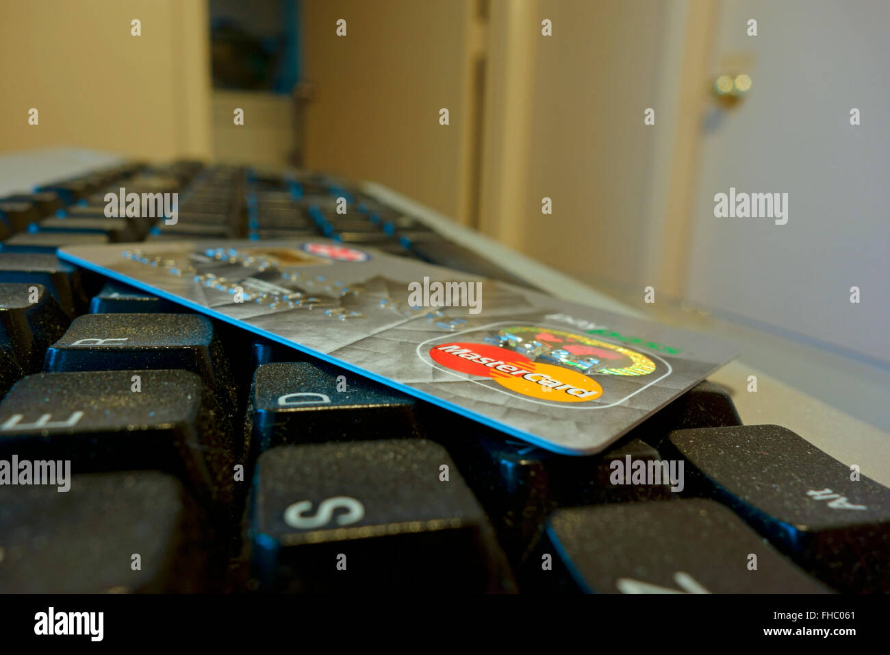 A Mastercard credit card lying on top of a computer keyboard - Stock Image
