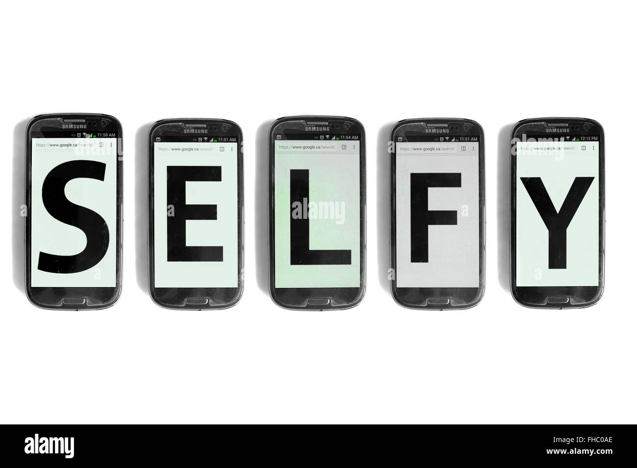 Selfy written on the screens of smartphones photographed against a white background. - Stock Image