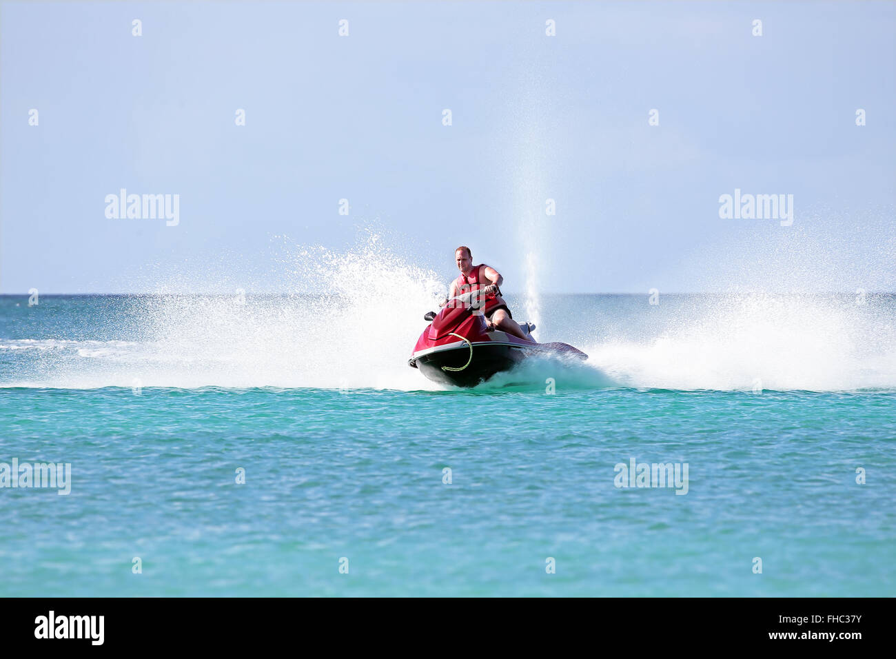 Young guy cruising on a jet ski on the caribbean sea - Stock Image